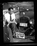 Nat Washington sitting on car fender by Hubert Blonk