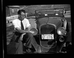 Nat Washington sitting on car fender
