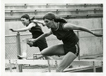 Two track member running hurdles by Publications, Eastern Washington State College