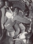 Soldiers preparing to parachute out of a plane by U.S.A. Army official photographer