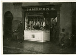 Serviceman and butcher talking at Cameron's storefront