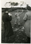 A paratrooper poses in a field for propaganda photographs by Robert Gillette