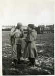 Major Barney Oldfield and paratrooper Robert Gillette in a field during a photo shoot