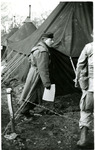 Major Barney Oldfield walking near a tent